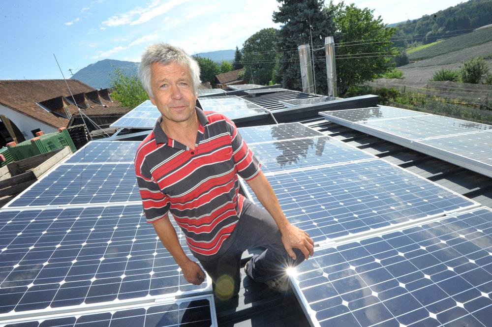 Josef Wilhelm inmitten seiner Photovoltaik-Anlage am Dach seines Biomasse-Heizwerks.
